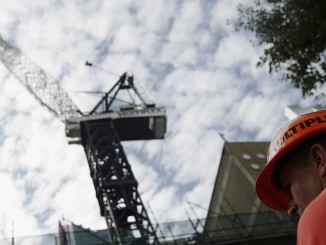 SYDNEY, NSW - APRIL 08:  A Mulitplex worker is seen next to one of the company's cranes April 8, 2005 in Sydney, Australia. Crane drivers for the company have ignored threats by an extortionist who has again threatened to kill crane drivers if $50 million AUD is not handed over.  (Photo by Ian Waldie/Getty Images)
