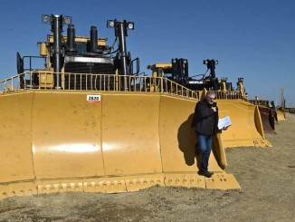 Randy Johnson of Calgary looks at his equipment list book as bidders survey the landscape at Ritchie Bros. heavy equipment auction on April 27, 2016 ED KAISER