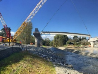 A concrete beam is lifted into place over the Waikanae river on the MacKays to Peka Peka section of the Kapiti expressway.