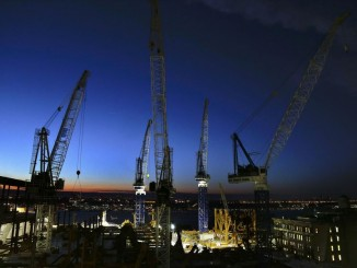 Cranes move loads of materials at dusk at the Hudson Yards construction site in New York on March 4, 2016. (Associated Press)