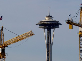 The Space Needle stands between two cranes in Seattle's South Lake Union neighborhood Friday, November 20, 2015. (Ellen M. Banner / The Seattle Times