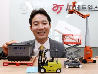 AJ Networks CEO Ban Chae-un holding a construction equipment miniature poses for a picture.