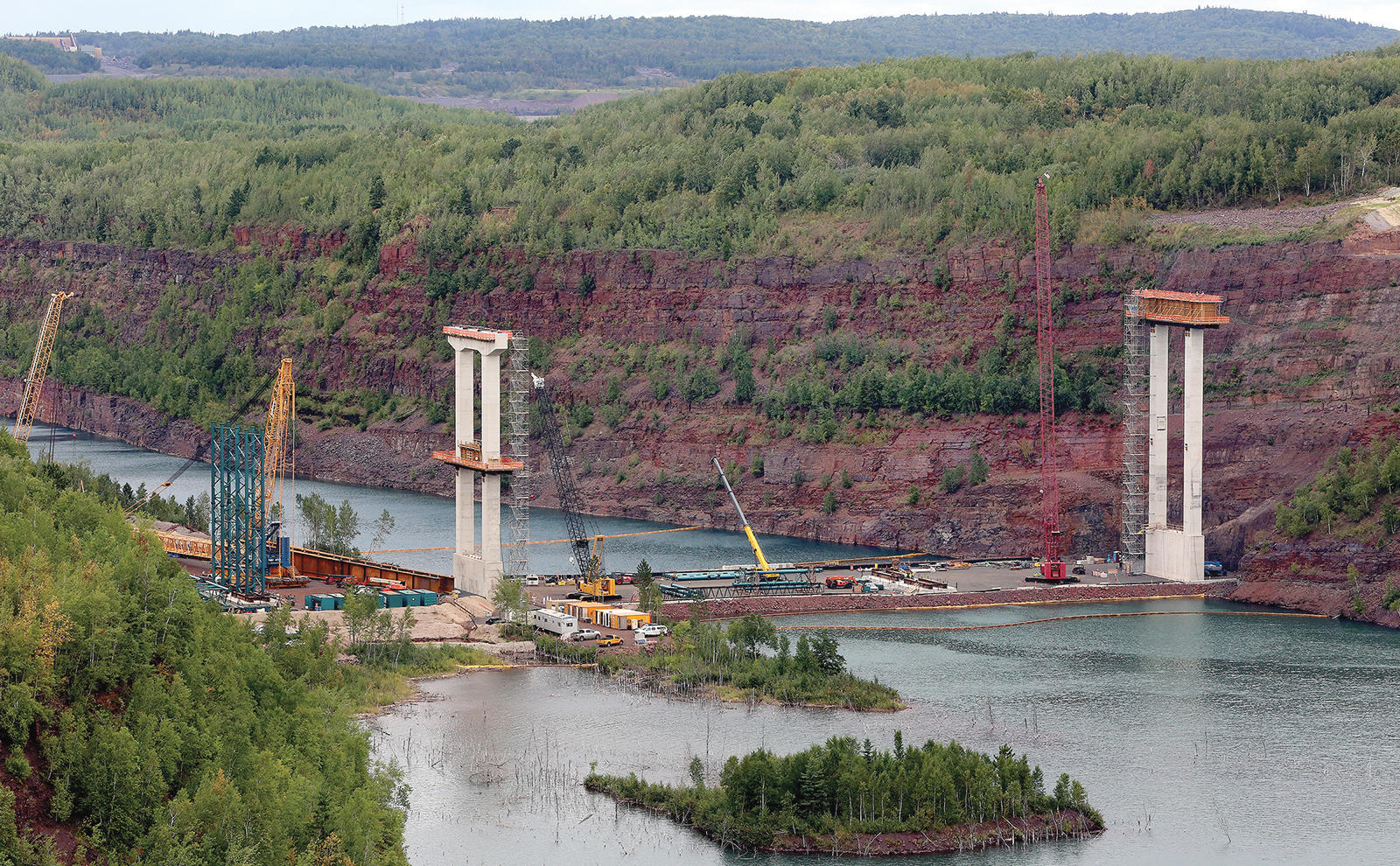 T08.24.2016 -- Steve Kuchera -- kucheraBRIDGE0827c3 -- The view from the location of the former Mineview in the Sky shows the concrete piers for the U.S. Highway 53 bridge being built across the Rouchleau pit rise above the pit's water. The temporary metal framework (left) will help support metal beams when they are lifted into place. Workers will build a second temporary metal framework to right. Steve Kuchera / skuchera@duluthnews.com