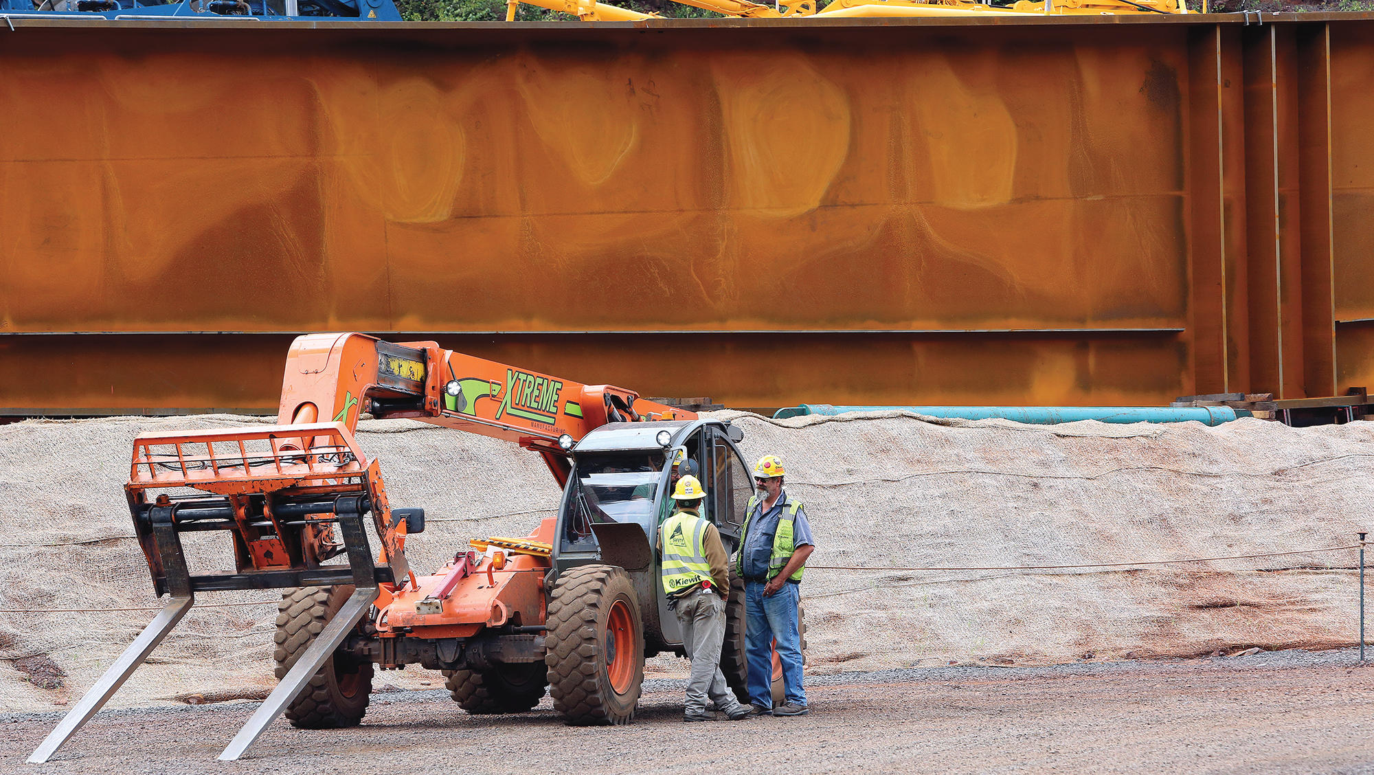 T08.24.2016 -- Steve Kuchera -- kucheraBRIDGE0827c4 -- Construction workers talk at a forklift near one of the steel beams that will help make the U.S. Highway 53 bridge being built across the Rouchleau pit. Made of two pieces bolted together, the beam is approximately 200 feet long and 15 feet tall. Workers are assembling the crane that will lift the bridge's beams into place. Steve Kuchera / skuchera@duluthnews.com