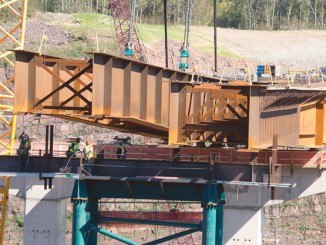 Iron Workers make sure that a set of steel beams weighing in at 750,000 pounds come to rest exactly where they should on the HWY 53 bridge being built in Virginia, MN.