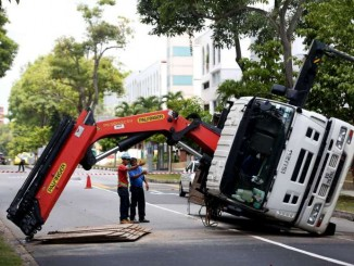 A Palfinger PH 50002-EH toppled loader crane tipped over dropping its load of steel plates on the road. The crane operator was slightly injured in the incident. PHOTO: THE NEW PAPER