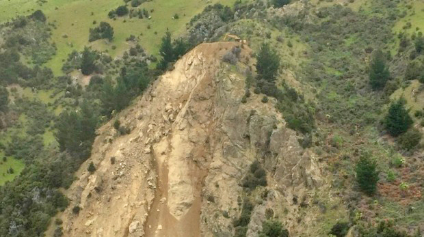 Spotted-a CAT Excavator atop a rock slide to repair severed road in New Zealand