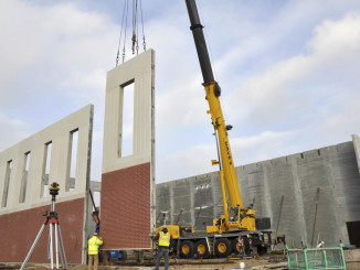 Workers help guide a 32-foot tall precast concrete panel into place forming the wall of the new Fort Dodge Senior High auxiliary gym. Seven similar panels stand next to it on this side of the gym, while nine form the completed far wall.