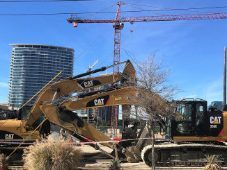 A Potain hammerhead crane towers above  John Burns Construction CAT excavators in downtown Dallas, TX.