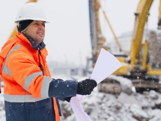 Civil engineer at construction site is inspecting ongoing works in  wintery conditions.
