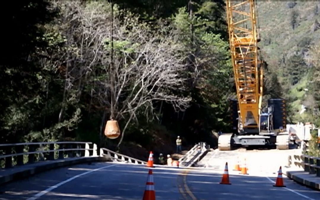 Liebherr crawler with wrecking ball trying  to bringing down condemned California Bridge in Big Sur