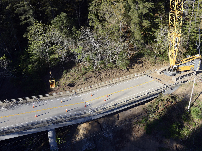 A crane operator moves a box over a fracture on the Pfeiffer Canyon Bridge in the early morning before adding wrecking ball to dismantle the structure on Highway 1 in Big Sur, Calif. on Monday March 15, 2017. The bridge was compromised after slides occurred in the area associated with this winter's heavy rains. (David Royal - Monterey Herald)