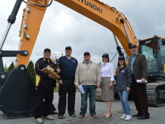 Jay Cornelsen, Jason Denis, Glenn Dredhart, Kimberly Norman, Cambria Bryce and Steve Kidd stand next to an excavator that will be used in competition this week. The group is promoting various activities that will be held during the Canadian Mining Expo on Wednesday and Thursday.