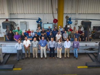 Link-Belt Cranes' Executive Staff and Boom Value Stream Team stand with the 10,000TH boom section produced at the Link-Belt formed boom bay in Lexington, Ky. The section is a boom base section for a 140-ton (127 mt) TCC-1400 telescopic crawler crane.