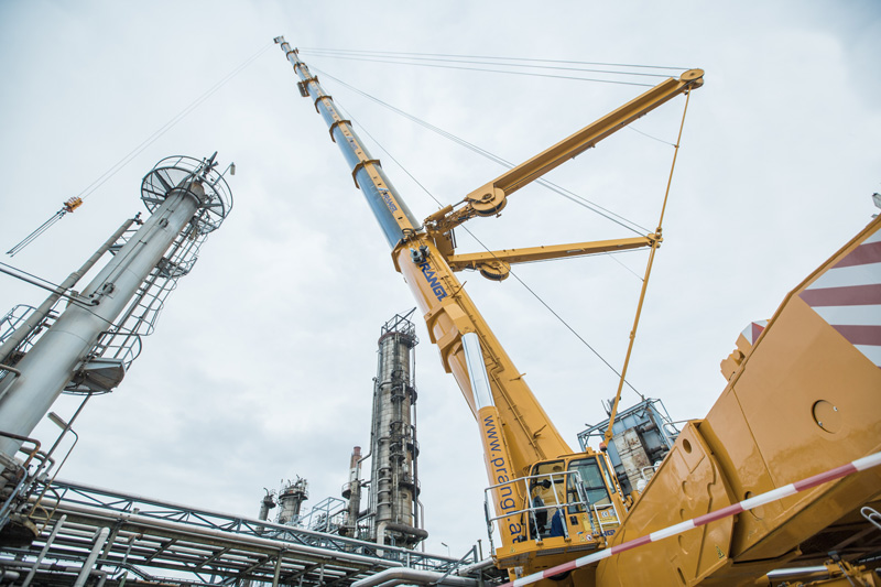 Prangl's Demag AC 1000-9 lifts the top section of fractionating column at refinery in Vienna, Austria