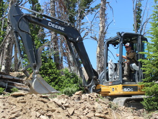 Pete Costain, owner of Terraflow Trail Systems, excavates dirt and rock on with a John Deere 50G mini excavator at Big Sky Resort in Montana. PHOTO BY DOUG HARE